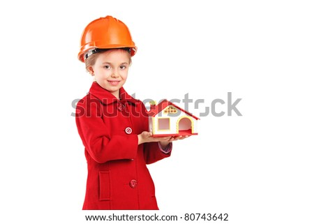 A child with helmet holding a model house isolated on white background