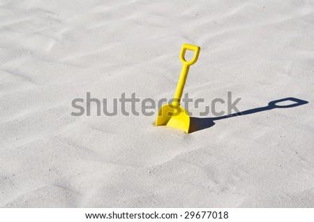 A child yellow toy shovel on a beautiful white sand beach. - stock photo