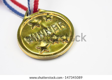 A children's plastic gold winners medal on a white background
