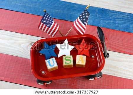 A childs toy wagon with red white and blue stars and blocks spelling USA. American Flags are behind the wagon on a patriotic red white and blue wood picnic table. Great for American holiday projects. - stock photo