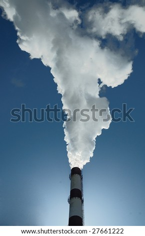 A chimney smoking right into the blue sky