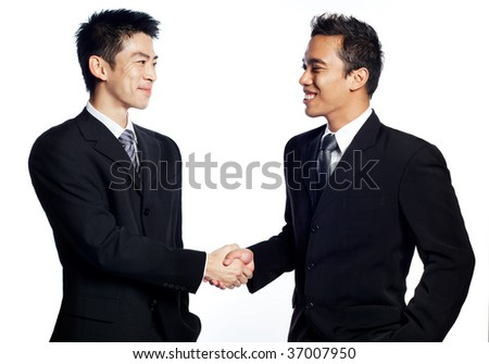 A Chinese, asian businessman shaking hands and smiling with an African business associate. Signifies the closing of deals. Shot in studio isolated on white - stock photo
