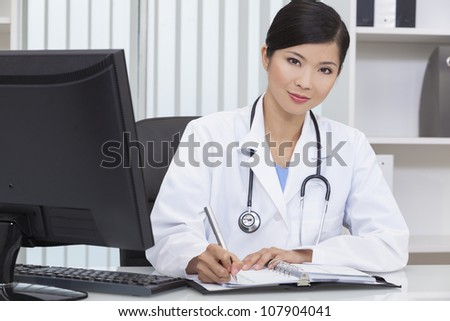 A Chinese Asian female medical doctor writing in a hospital office - stock photo