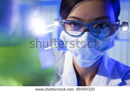 A Chinese Asian female medical or scientific researcher or doctor looking at a flask of green liquid in a laboratory.