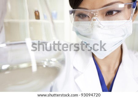 A Chinese Asian female medical or scientific researcher or doctor using looking at a conical flask of clear liquid in a laboratory - stock photo