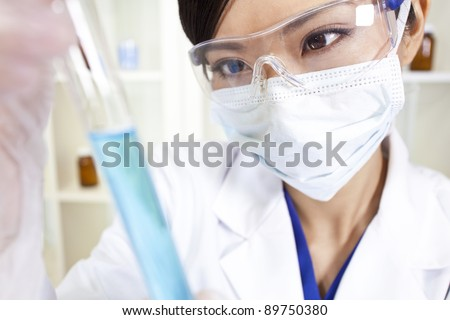 A Chinese Asian female medical or scientific researcher or doctor using looking at a test tube of blue liquid in a laboratory - stock photo