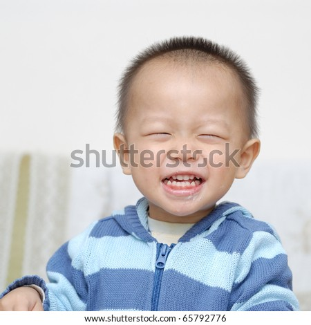 A chinese boy is laughing. he just eat a cake, and some cake scrap is still on his mouth - stock photo