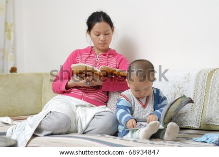 A chinese family, the mother and the boy are reading the book in home.