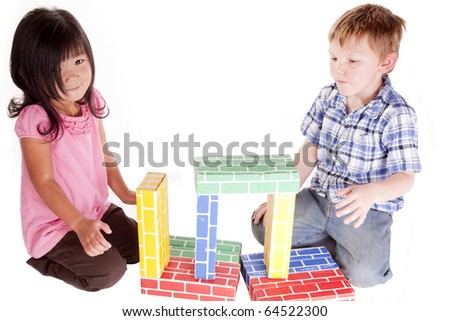 A chinese girl and a caucasion boy are playing with blocks. - stock photo