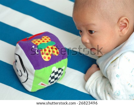 A chinese infant is palying with his toy, his eyes focus on the toy.