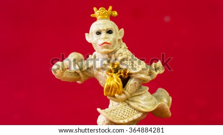A chinese new year's ceramic figure represent a year of monkey holding gold ingot represent long live, prosper and good luck. Slightly de-focused and close-up shot. Copy space. - stock photo