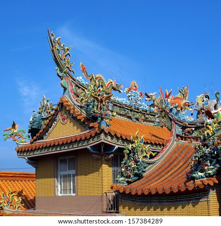 A Chinese temple with colorful decorations of mythological beasts  - stock photo