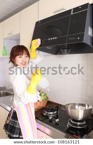 A Chinese woman is cleaning in the kitchen. - stock photo