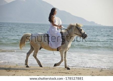 a Chinese young woman riding horse on beach - stock photo