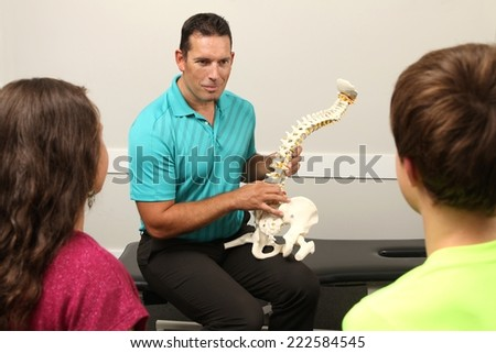 A Chiropractor showing a model of the human spine to two children - stock photo