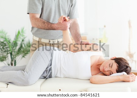 A chiropractor stretches a female customer's arm in his surgery - stock photo