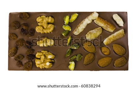 A chocolate bar with chesnuts, almonds, raisins, pistachi and candied orange, isolated on white.