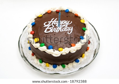 A chocolate birthday cake with candy, candle and icing. - stock photo