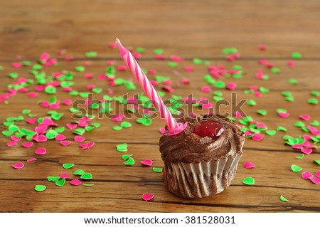A chocolate cupcake with a birthday candle displayed on a table with colorful confetti