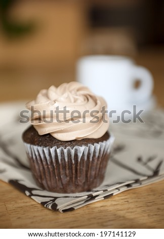 A chocolate cupcake with frosting on a linen napkin placed on a wooden table.
