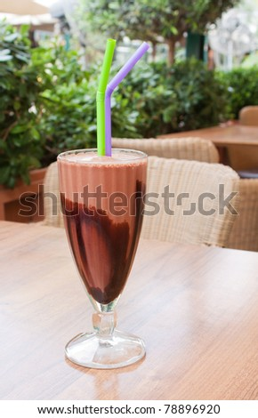 A chocolate milkshake on an outside table of a cafeteria. - stock photo