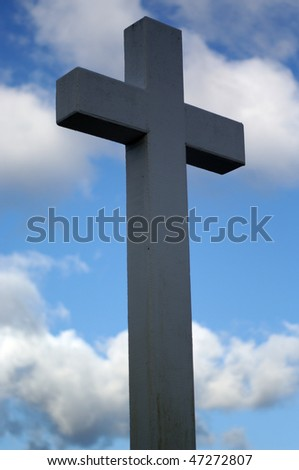 A Christian Cross against the background of a blue sky with white clouds.