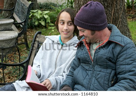 A christian youth explaining the bible to a homeless man. - stock photo