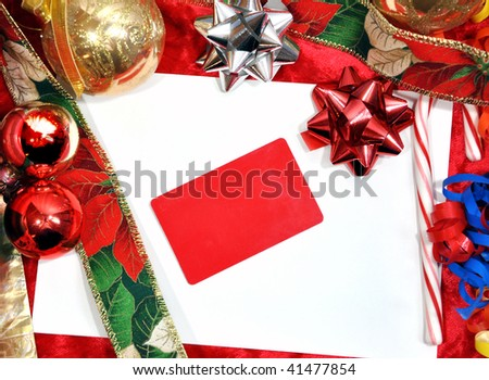 A Christmas background with a blank white envelope and a red gift card on top of it. Add your text to the card. Christmas and holiday objects surround the image.