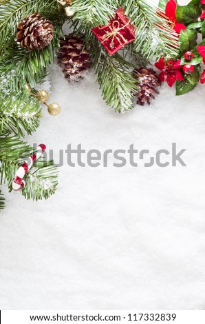 A Christmas border to left and top of frame consisting of artificial foliage, real pine cones and decorative ornaments, sprinkled with snow on a fake snow background.   Snow provides copy space. - stock photo
