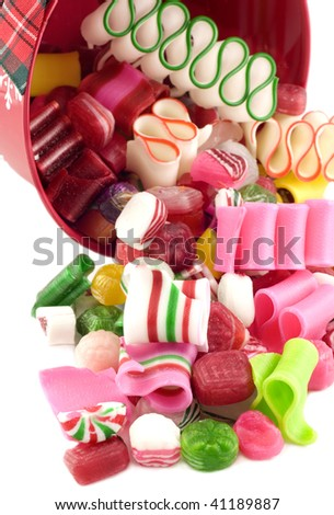 A Christmas bucket with candy spilling out, white background, selective focus, vertical with copy space - stock photo