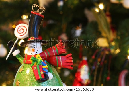 A christmas decoration in the form of a snowman, waving and holding christmas presents, decorated christmastree in background - stock photo
