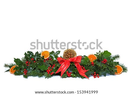 A Christmas garland made from fresh holly with red berries, dried orange segments, green ivy, conifer sprigs and pine cone, finished off with a red ribbon and bow. Isolated on a white background. - stock photo