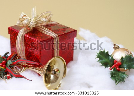 A christmas gift box wrapped in a golden ribbon in a holiday scene. - stock photo