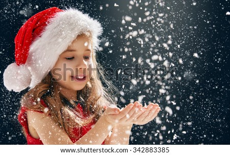 a Christmas miracle! happy little girl catching snowflakes in her hands - stock photo