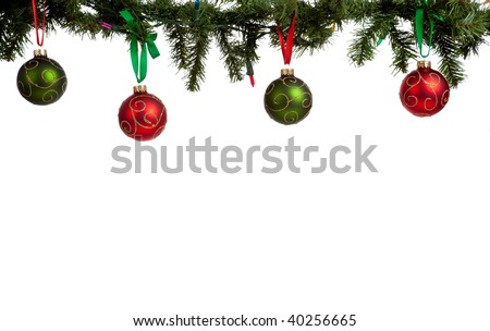 A christmas ornament border with red and green glittered baubles hanging from garland with red and green ribbon - stock photo