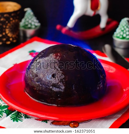 A Christmas pudding with burning brandy topping, copy space for your text - stock photo