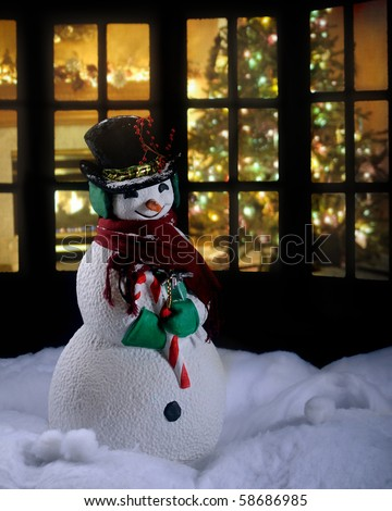 A Christmas snowman in the snow at night with a living room decorated for the holidays seen through a silhouetted window behind him.  Intentionally dark for nighttime lighting. - stock photo