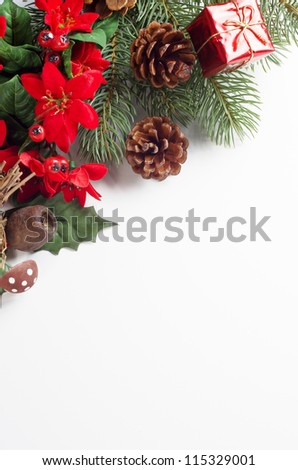 A Christmas themed border running diagonally from mid-left to upper right of frame consisting of a variety of artifical flora decorations with a shiny tied gift box and real fir cones. - stock photo