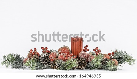A Christmas themed flower arrangement with a red candle isolated on a white background. - stock photo