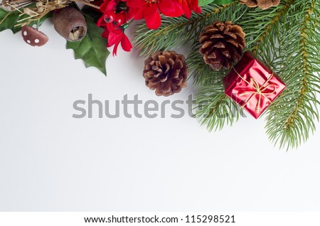 A Christmas themed top frame border , made up of a variety of artifical Winter flora decorations in greens, reds and browns, with a shiny tied gift box and real fir cones. - stock photo