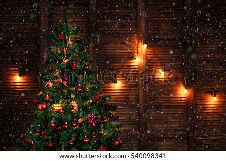 a Christmas tree decorated with toys ornaments beads red garland on wooden brown wall copyspace