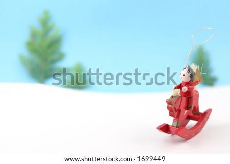 A Christmas tree decoration sets off across a snowy landscape on horseback - stock photo