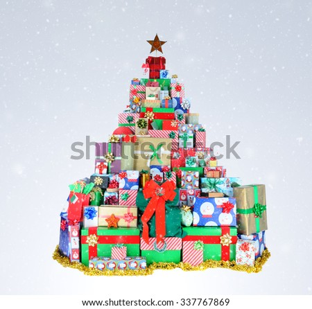 A Christmas tree shape made up of many stacked presents, on a light to dark snowy background. - stock photo