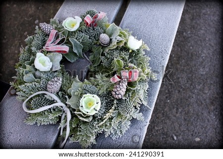 A Christmas / Winter wreath on a bench in the frost - stock photo