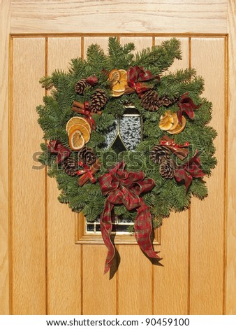 a christmas wreath with pine cones orange cinnamon sticks and ribbon on a new wooden door