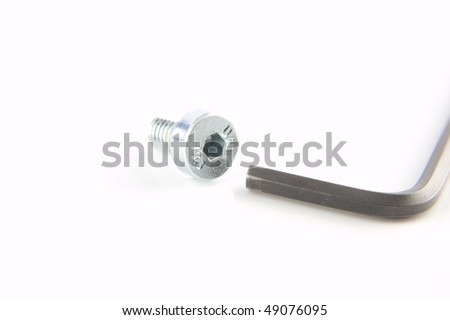 A chrome cap head or allen screw with a wrench ready to tighten - stock photo