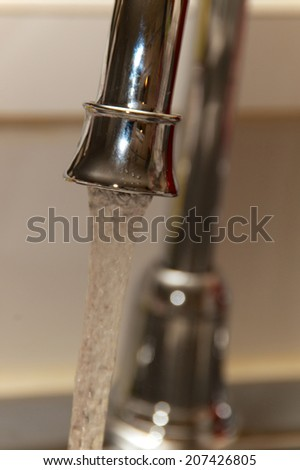 A chrome kitchen water faucet up close with water running. - stock photo