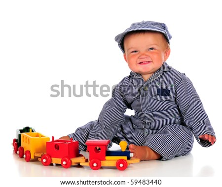 A chubby baby boy in striped coveralls and hat happily playing with a colorful wooden train.