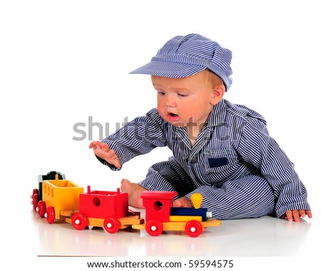 A chubby baby boy in striped overalls and hat playing with a colorful wooden train.  Isolated on white.