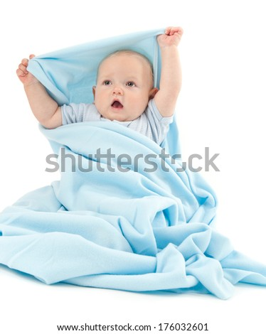 A chubby cheeked baby wrapped in a blanket with his arms over his head. - stock photo